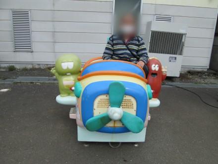 酪農王国オラッチェ 子供の乗り物に乗る男